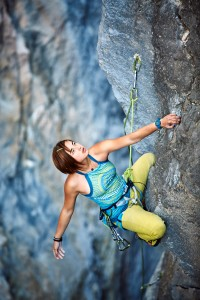 female rock climber climbs on a rocky wall